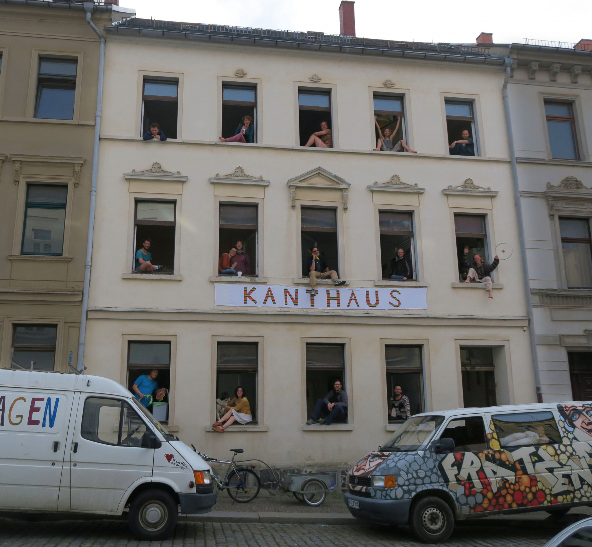 A street-view of an old building with happy people waving out of the windows.